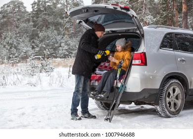 Father pouring hot drink for child after sports activities such as ski. Sitting back trunk of suv at winter season. Copyspace