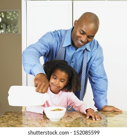 Father pouring milk into daughter's cereal