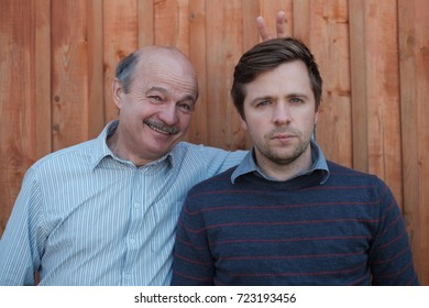 Father pranking his son with bunny ears isolated on wooden background. Young nman is very serious, old gentleman smiles.