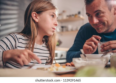 Father preparing breakfast for daughter in the kitchen at home