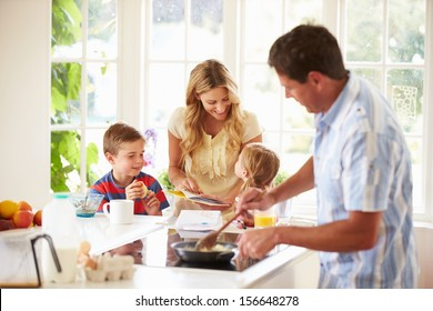 Father Preparing Family Breakfast In Kitchen