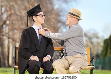 Father preparing his son for graduation seated on wooden bench in park