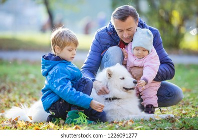 Father with preschool son and baby daugther playing with samoyed dog in autumn park