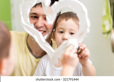 Father and preschooler son draw heart shape on mirror with shaving foam playing in bathroom
