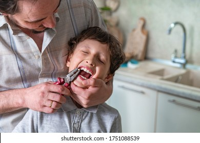 father pulled out his son's baby tooth with a pliers construction tool. concepts of self-treatment at home. the child lost a tooth.