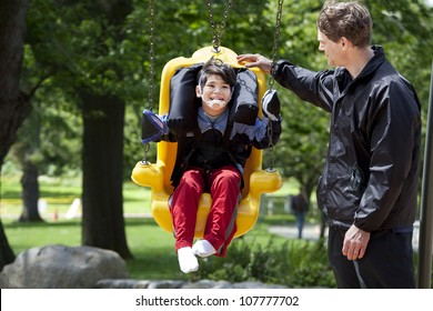 Father pushing disabled boy in special needs handicap swing. Child has cerebral palsy.