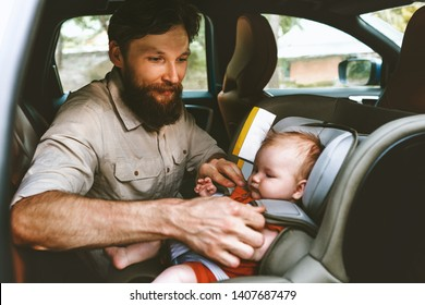 Father putting baby in safety car seat happy family vacation road trip lifestyle child care transportation rear-facing