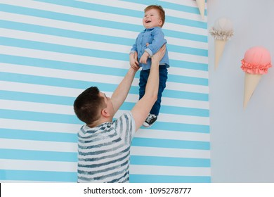 Father raise his little son on his hands on white and blue stripe background. Playing in babyroom