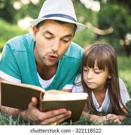 Father reading a book to his daughter while laying outdoor on the grass