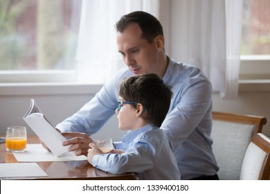 Father reading book to son aloud at kitchen at home. Daddy help boy to study on weekend, teaching, reading story, fairy tale together. Happy family spending time together, leisure time concept
