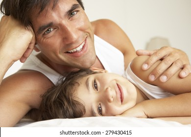 Father Relaxing With Son In Bed