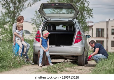 father replacing a damaged family car tire.