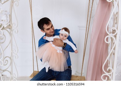 The father rolls his little girl. He watches with interest her reaction and emotions. A little girl is riding on a swing for the first time.