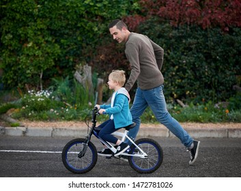 Father running teaching his son how to cycle ride a bicycle, helping balance
