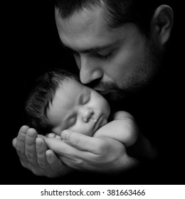 Father 's love.  Daddy kisses his newborn baby. Close-up portrait on a black background