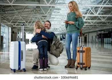 Father saying goodbye to his wife and daughter at the airport. He is hugging the child. Their faces expressing joy