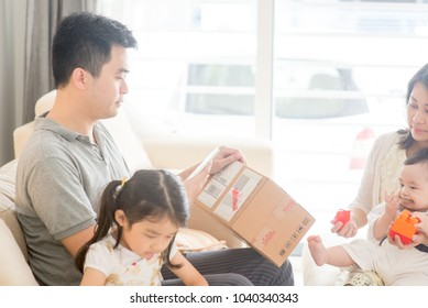 Father scanning QR code with smart phone. Happy Asian family at home, natural living lifestyle indoors.