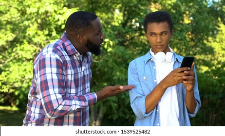 Father scolding male teen son playing smartphone game ignoring parent upbringing