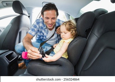 Father securing baby in the car seat in his car