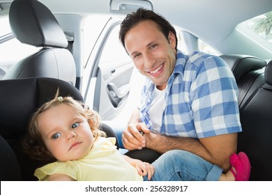 Father securing his baby in the car seat in his car