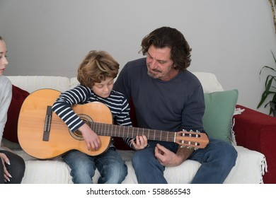Father showing his little son how to play guitar