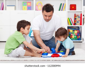 Father showing his sons a new toy - examining it together