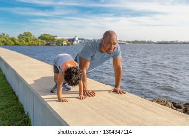A father is showing his young son how to do pushups on the seawall at the intercoastal. The young father is teaching his little by the importance of good health and exercise.