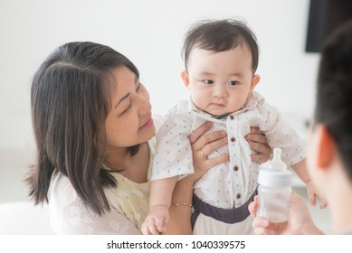 Father showing milk bottle to baby. Happy Asian family at home, candid living lifestyle indoors.