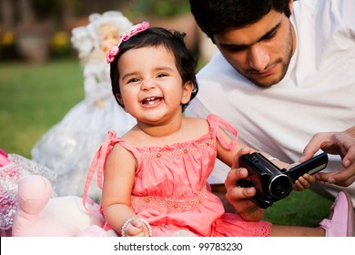 father showing pictures to his daughter on digital camera, biracial family