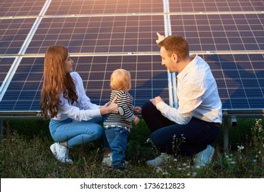 Father shows his family the solar panels on the plot near the house during a warm day. A young girl with a child and a man in the sun rays look at the solar panels.