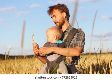 father shows his son (infant baby in sling) the ear of barley, Russia