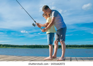 father shows his son on the pier how to hold a fishing rod to catch fish, against the blue lake and sky
