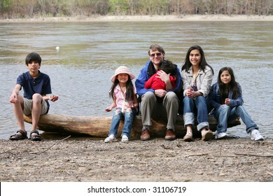 Father sitting with his children on fallen log