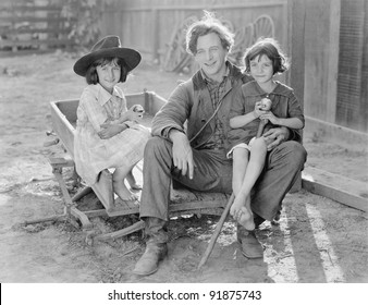 Father sitting with his two daughters on a small wagon on a farm
