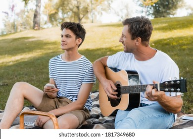 father sitting on blanket and playing acoustic guitar near teenager son with smartphone