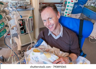 A father sitting on a chair in a intensive care unit holding his sick infant boy wrapped in a blanket surrounded by medical equipment.