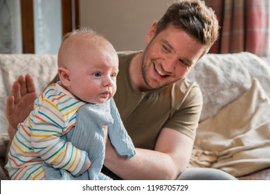 Father sitting on the edge of the sofa in the living room and burping her newborn child after feeding him.