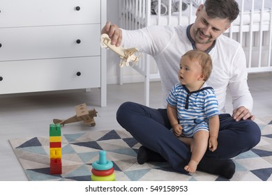Father sitting on the floor with his child and showing him a wooden plane