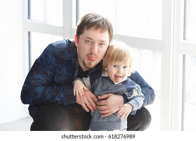 Father sitting on the floor with his child and having fun. Dad with two years old baby boy spending time together.