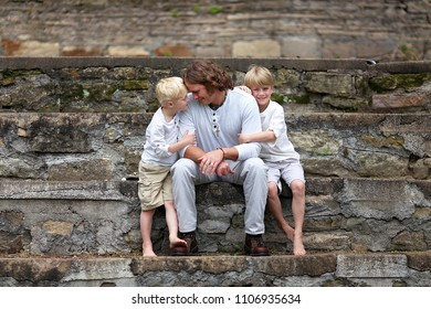A father is sitting outside with his two young children, lovingly looking into the eyes of his little son.