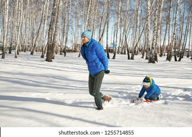 father sledding his son in the winter. people for a walk outdoors