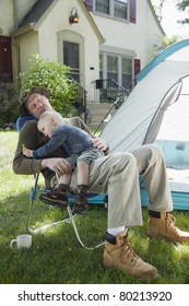 Father sleeping with son in his lap while camping in the front yard