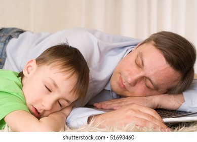 father sleeps with son on laptop