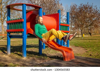 Father sliding in public playground, Zagreb, Croatia.