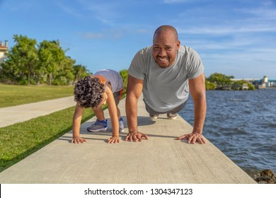 A father smiles as he shows his young son how to do pushups on the seawall at the intercostal. The young boy looks at dad teaching him to exercise as part of good health.
