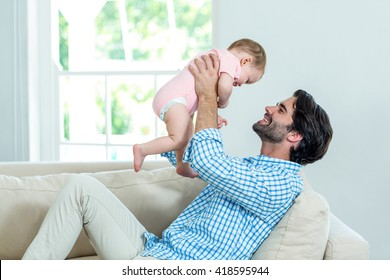 Father smiling while playing with son on sofa at home