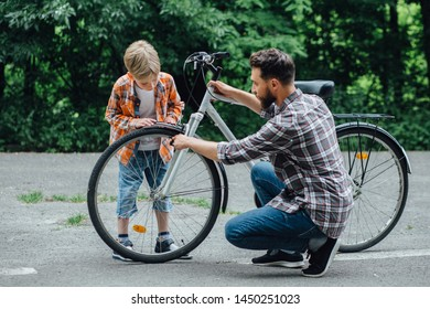 Father and Son, 7 year old boy, are spending quality time together fixing wheel bike. They are in a park road, trees behind them with a bicycle between them