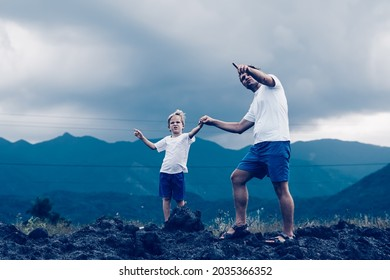 Father son or adult younger brother walk. Cloudy sky before rain, mountain background. Man show points finger into distance, serious boy look far away. Solve problems together. Natural education