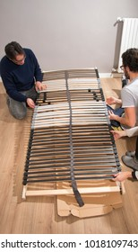 Father and son assembling bed in a new house