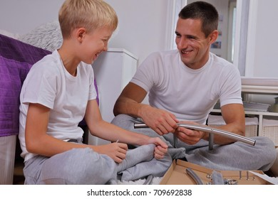 Father and son assembling furniture . Boy helping his dad with building work at home. Happy Family concept.